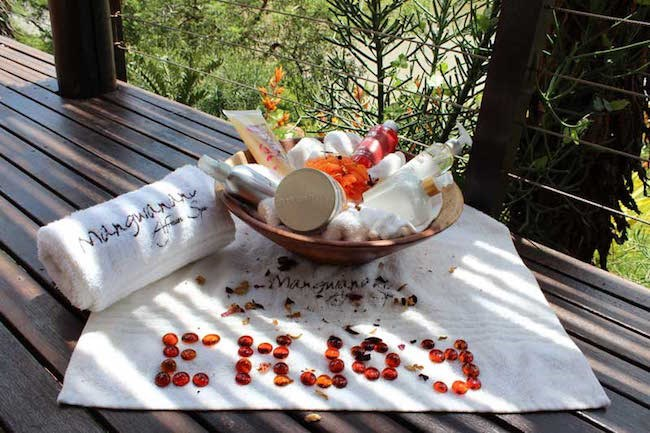 A Mangwanani Spa sundeck feature with white towels, relaxing spa products and red pebbles