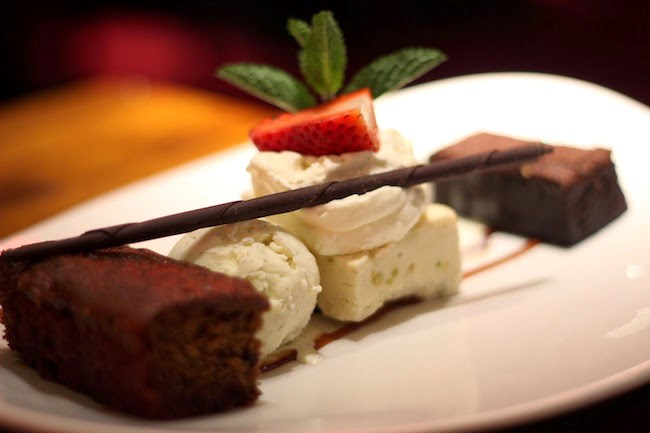 A gourmet chocolate dish with ice cream, cake and strawberries on a white plate