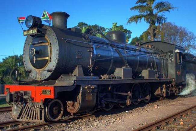 The black and orange Umgeni steam train on the railway track