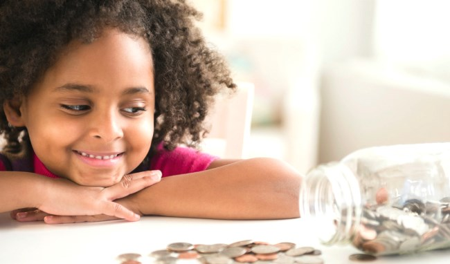 A young girl smiling at her jar full of saved money during a lesson of money management by her parent