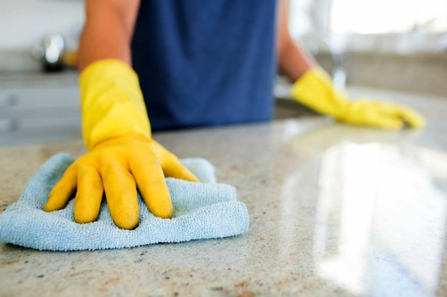 Shining a kitchen counter with yellow cleaning gloves and a blue cloth