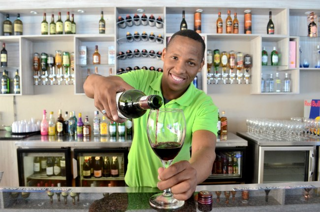 Barman pouring drinks at restaurant in PE