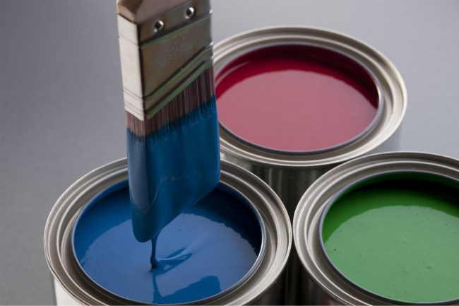 Blue, red, green paint tins with paint brush