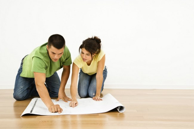 A man and woman on their hands and knees, looking at floor plans next to a wall