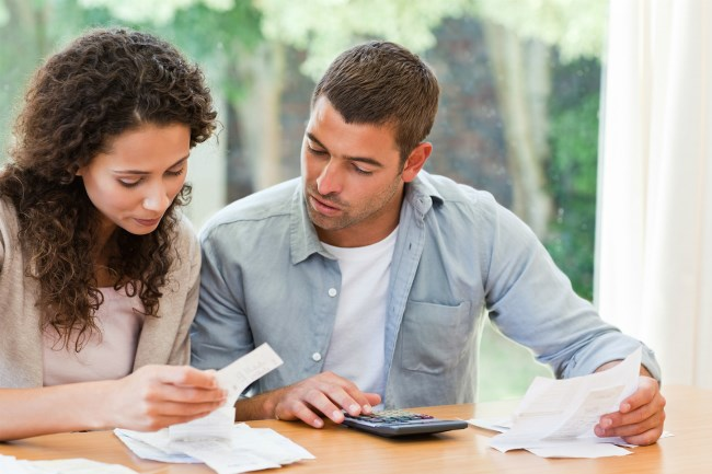 Couple sitting at a table calculating their finances / home buying budget plan