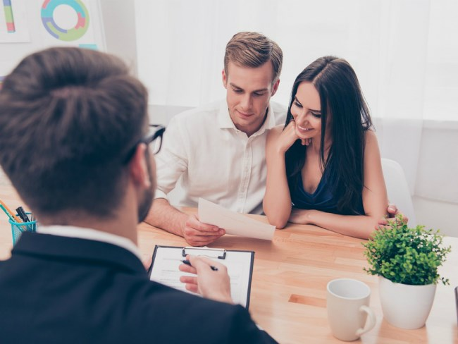 Home buying couple sitting with a real estate agent at a table