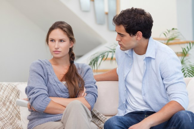 couple sitting on a couch, arms crossed with upset expressions on their faces