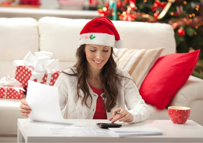 Lady sitting at table calculating christmas budget