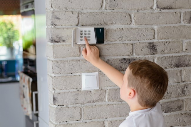 kid using the security alarm system at home